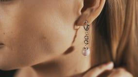 Beautiful woman puts on beautiful earrings. Close up stock footage