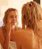Beautiful woman puts a face cream after a shower Stock Image