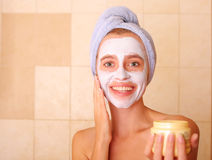 Beautiful woman puts on the face a mask Stock Image