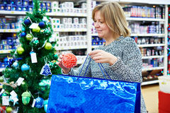 Beautiful woman puts  red Christmas ball on holiday blue bag Stock Photos