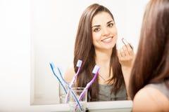 Beautiful woman putting lipstick on Stock Photo