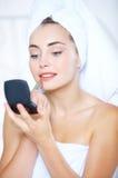 Beautiful woman putting on lipstick Royalty Free Stock Image