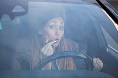 Beautiful woman putting on lipstick in car stock image