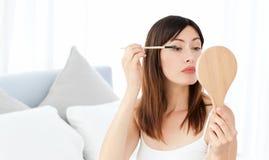 Beautiful woman putting on Make up Stock Photos