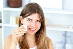 Beautiful woman putting make-up on her face Stock Photography