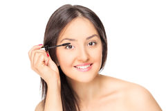Beautiful woman putting on make-up Stock Image