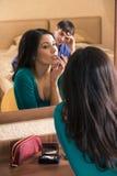 Beautiful woman putting make up Stock Photography
