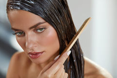 Beautiful Woman Putting Mask On Long Wet Hair. Hairbrushing. Hair Beauty. Closeup Of Beautiful Woman Hairbrushing With Comb And Using Conditioner. Young Female Royalty Free Stock Image