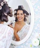 Beautiful woman putting on morning make Stock Images