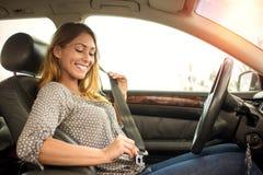 Beautiful woman putting on seatbelt Royalty Free Stock Photos