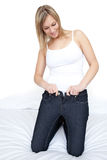Beautiful woman putting on tight jeans on a bed Royalty Free Stock Images