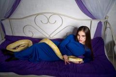 Beautiful woman with python. Bright photo, studio shoot, beautiful woman with long light hair, holding wild albino python, lie on bed. Erotic emotional Stock Photo
