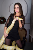 Beautiful woman with python. Beautiful girl in lace black dress is in the studio room. It is on a large table desk holding a huge white albino python, which Stock Image