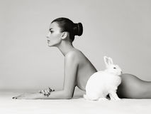 Beautiful woman with rabbit. Studio fashion photo of naked elegant lady with white rabbit Royalty Free Stock Image