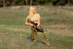 Beautiful woman ranger with rifle in camouflage stock image