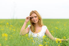 Beautiful woman in rape field Stock Photos