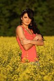 Beautiful woman in a rapeseed field. Beautiful brunette posing in a rapeseed field at sunset, she has a red undershirt and heart on a chain, spring – May Royalty Free Stock Photo