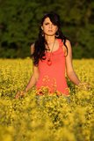 Beautiful woman in a rapeseed field. Beautiful brunette posing in a rapeseed field at sunset, she has a red undershirt and heart on a chain, spring – May Stock Photography