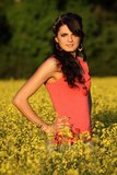 Beautiful woman in a rapeseed field. Beautiful brunette posing in a rapeseed field at sunset, she has a red undershirt and heart on a chain, spring – May Stock Images