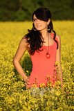 Beautiful woman in a rapeseed field. Beautiful brunette posing in a rapeseed field at sunset, she has a red undershirt and heart on a chain, spring – May Royalty Free Stock Photos