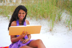 Beautiful woman reading on the beach Stock Photo