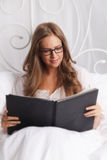 Beautiful woman reading in the bed Stock Image