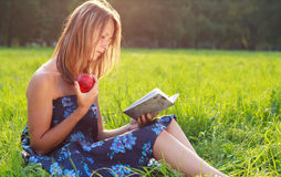 Beautiful woman reading book with apple in hand Stock Photo