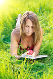 Beautiful Woman Reading Book with Apple in Hand Stock Images