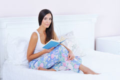 Beautiful woman reading a book in bed Royalty Free Stock Image