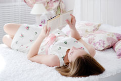 Beautiful woman reading a book in bed Stock Image
