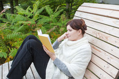 Beautiful woman reading book on bench Royalty Free Stock Photos