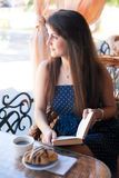 Beautiful woman reading a book in the cafe Royalty Free Stock Image