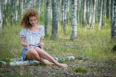 Beautiful woman reading book in forest Royalty Free Stock Photography