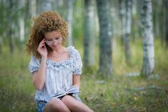 Beautiful woman reading book in forest Royalty Free Stock Images