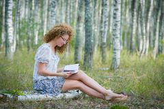 Beautiful woman reading book in forest Royalty Free Stock Photos