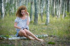 Beautiful woman reading book in forest Stock Images