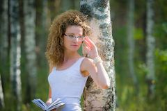 Beautiful woman reading book in forest Royalty Free Stock Image