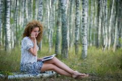 Beautiful woman reading book in forest Stock Image