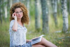Beautiful woman reading book in forest Stock Photography