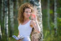 Beautiful woman reading book in forest Royalty Free Stock Photo