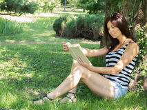 Beautiful woman reading a book. In the green garden Stock Images