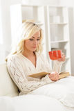 Beautiful woman reading a book and having a cup of coffee Stock Images