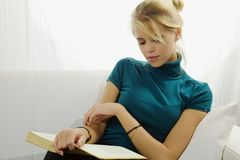 Beautiful woman reading book at home relaxing Stock Photography