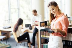 Beautiful woman reading a book in a library Stock Photos