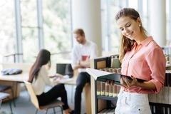 Beautiful woman reading a book in a library Stock Images