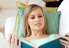Beautiful woman reading a book lying on a sofa Stock Photo