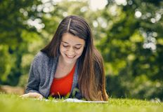 Beautiful woman reading book in nature. Young attractive student in red dress studying and reading a book. Relax, rest, education concept, recreation Royalty Free Stock Photography