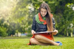 Beautiful woman reading book in nature. Young attractive student in red dress studying and reading a book. Relax, rest, education concept, recreation Royalty Free Stock Images