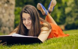 Beautiful woman reading book in nature. Young attractive student in red dress studying and reading a book. Relax, rest, education concept, recreation Royalty Free Stock Photos