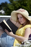 Beautiful woman reading. A Beautiful woman reading a book outside on a balcony holding her hand on a sun hat. Sitting on a sofa relaxing Stock Photos